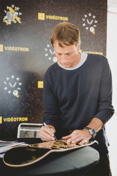 Tony Hawk signing a skateboard